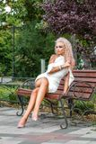 High fashion shot of young blond woman in white short dress royalty free stock image