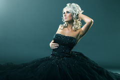 High fashion woman in sexy pose and  large formal dress sitting Royalty Free Stock Photos