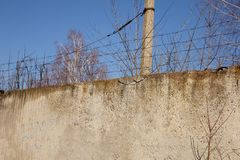 High fence closes the object, fenced with barbed wire. royalty free stock photo