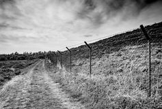 High, barbered-wire and partially electrified fencing seen at a border area, known for illegal immigration. This high fence extended to the background, and has royalty free stock image
