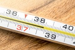 High fever and body temperature. Having fever, flu, sickness, virus and being sick concept. Macro close up of thermometer with celsius numbers stock photography