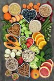 High Fiber Health Food. High fibre health food concept with whole wheat pasta, legumes, cereals, grains, fresh fruit & vegetables on marble background top view royalty free stock photo