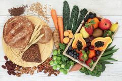 High Fibre Food for a Healthy Life. High fibre healthy food concept with wholegrain bread and rolls, nuts, seeds, fruit, vegetables and grains with foods high in stock photos