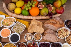 High Fibre Food. Selection of high fibre foods including fruit, vegetables, wholemeal bread, pasta, seeds and nuts royalty free stock photography