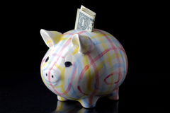 High Finances. A dollar bill is half way into the slot of a child's piggy bank. The piggy bank is a colorful plaid and is home made. The background is black Stock Photos