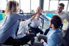 High-five! cheerful young business people giving high-five while their colleagues looking at them and smiling. stock photos