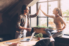 High-five!. Cheerful young men and women giving high-five while having coffee break in creative office stock images