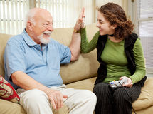 High Five for Grandpa. Teen girl playing video games, getting a high five from her grandfather Stock Images