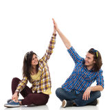 High Five. Happy boy and girl sitting on the floor with legs crossed and giving high-five to each other and smiling. Full length studio shot isolated on white royalty free stock photo