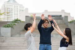 High five. Laughing excited teen friends giving high five Royalty Free Stock Photos