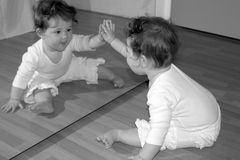 High Five Mirror BW. Baby Girl making faces and playing in the mirror royalty free stock image
