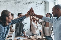 High-five for success! Diverse group of business colleagues giving each other high-five in a symbol of unity and smiling while royalty free stock photography