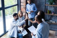 High-five for success Diverse group of business colleagues giving each other high-five in a symbol of unity and smiling. While working in the office royalty free stock image