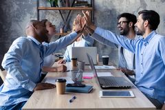 High-five for success Diverse group of business colleagues giving each other high-five in a symbol of unity and smiling. While working in the office stock photography