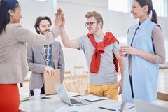 High five. Two successful managers giving high five over table after making business agreement Royalty Free Stock Photography