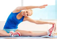 High flexibility. Smiling woman with high body flexibility exercising in the gym Royalty Free Stock Photography