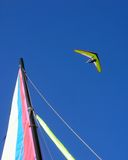 High flier. Man flying hand glider over sail Stock Photo