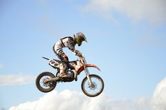High flight of motorcycle racer on a motorcycle. RUSSIA, SAMARA, CHAPAYEVSK - OCTOBER 17: High flight of motorcycle racer E.Pershin on the background of clouds royalty free stock images