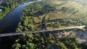 High flight over the field, river, bridge with cars.