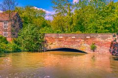 High flood water under a bridge over the Great Stour river in Ca. High flood water of the Great Stour river under a bridge in Canterbury, Kent, Uk on a sunny day royalty free stock images