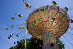 High flying fun at the amusement park. Young people enjoy the excitement and exhilaration of the high flying swings on a ride at the amusement park at a fair in stock image