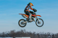 High flying motorcycle racer on blue sky background Stock Photography