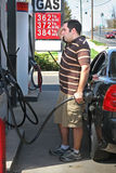 High Gas Prices. A man pumping high priced gas into his car with a disgusted look on his face Stock Image