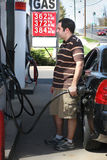 High Gas Prices. A man pumping high priced gas into his car with a disgusted look on his face Royalty Free Stock Photos