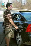 High Gas Prices. A man pumping high priced gas into his car with a disgusted look on his face Stock Photos