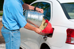 High gas prices - pouring money into gas tank. Man pouring bucket of cash into his gas tank symbolizing economic hardship just to purchase gas and petroleum Royalty Free Stock Image