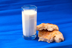 High glass of milk and white bread pieces on blue. Glass of milk and white bread pieces on blue background Stock Image