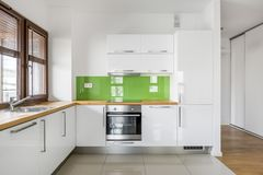 High gloss, white kitchen with wooden window. High gloss, white kitchen with big window, wooden countertop and modern, green backsplash royalty free stock images