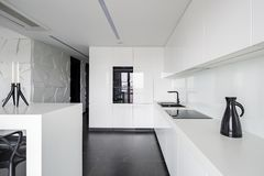 High gloss elegant white kitchen. With modern equipment and black flooring stock photos