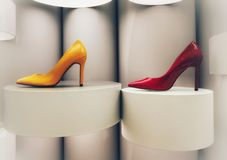 Yellow and red stiletto on display. High gloss yellow and red high heels on clean white display royalty free stock photos