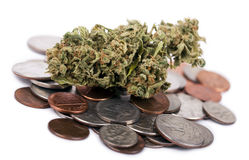 Marijuana & Change. A high grade hydrophonic Cannabis (Marijuana) bud resting on a pile of various USA coins - pennies, quarters, dimes, nickels. White Royalty Free Stock Photos
