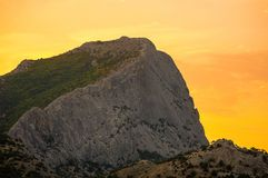 High gray mountain with a flat slope covered with greenery in orange light dawn of the sun. High gray mountain with a flat slope covered with greenery in orange Royalty Free Stock Image