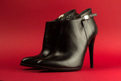 High heel black shoes on red background Stock Photography