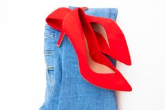 High heel red shoes on heels with blue jeans on white background royalty free stock photo