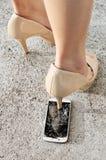High heel shoe crushing a smart phone. Royalty Free Stock Photo
