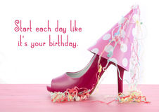 High Heel Shoe with Famous Quote. Pink high heel shoe on pink wood shabby chic table with Start Each Day Like Your Birthday quote Stock Photos