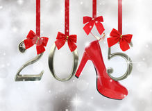 High heel shoe and 2015. Number hanging on red ribbons in a glittery background stock image