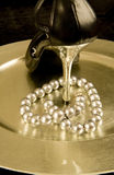 High heel shoe and pearls on a silver tray Royalty Free Stock Image