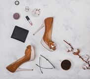 High heel shoes, coffee and small feminine accessories on the ma royalty free stock images