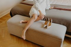 High heel shoes and feet close up. Woman in white dress, sits bare foot on comfortable sofa, rests at home after work. Feminity an. D footwear concept royalty free stock photography