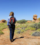 High Heel Walking Woman in Outback Australia. A mature woman in black high heel shoes and a backpack over her shoulder walking through the wilderness of outback Royalty Free Stock Image