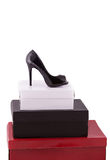 High-heeled black shoe on some boxes Stock Photography