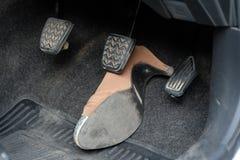 High-heeled schoen onder rem wordt geplakt die Stock Foto's