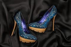 High-heeled shoes  lying on black  fabric Stock Image