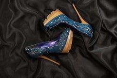 High-heeled shoes  lying on black  fabric Stock Photos