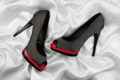High-heeled shoes lying on white  fabric Stock Image